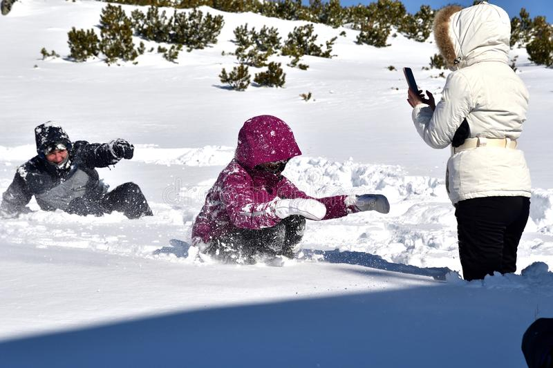 Family playing tumble on the snow in mountains. Family to climb and tumble on the snow in mountains stock images