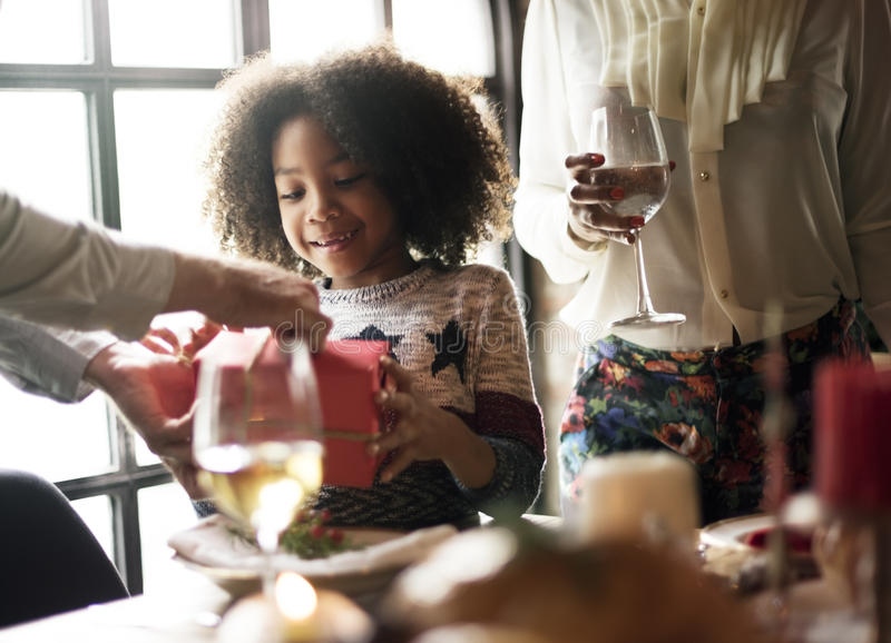 Family Together Christmas Celebration Concept. African descent girl receiving holiday gift stock photography
