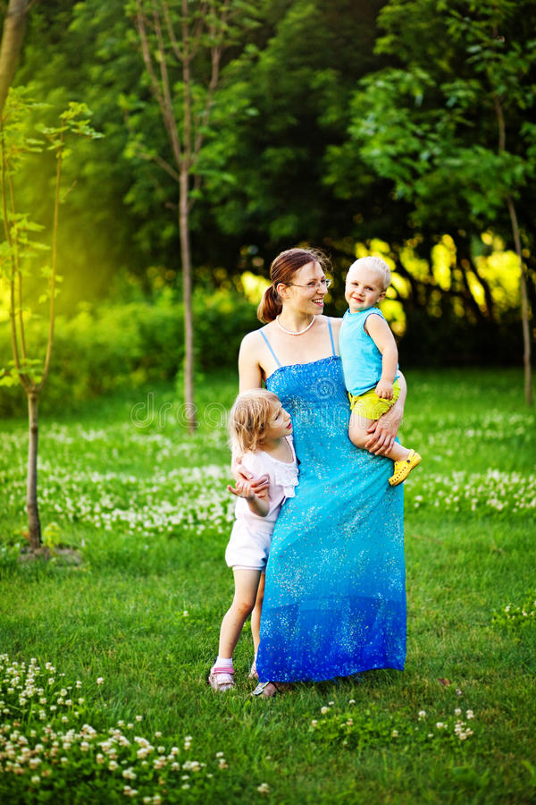 Family together in the park. Mother hugging her kids in the park stock photo