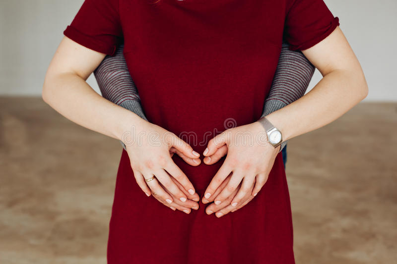 Family together. Woman is pregnant. The husband and wife, lovers dressed in a Burgundy style. Young attractive couple. Family together in Woman is pregnant royalty free stock images