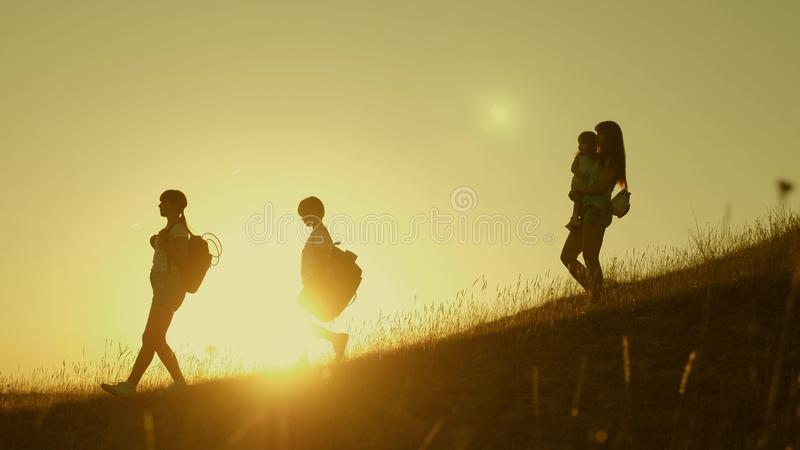 Family of tourists with children traveling at sunset. children and mom with backpacks travel down mountains in rays of stock photos