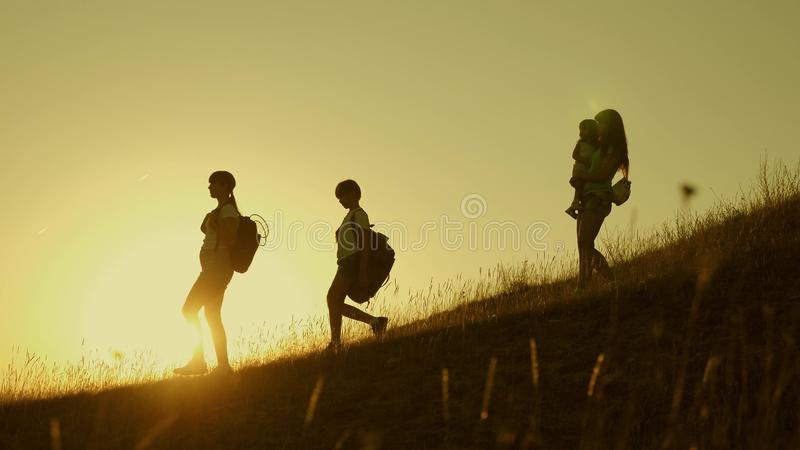Family of tourists with children traveling at sunset. children and mom with backpacks travel down mountains in rays of royalty free stock photo