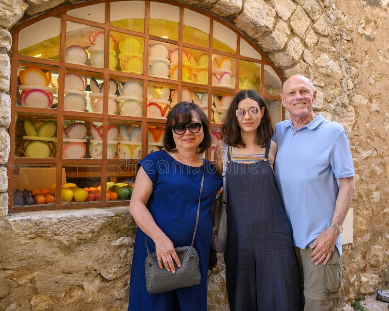 Family of tourists in front of candle shop, Gourdon Village perched on a rocky outcrop, France royalty free stock photos