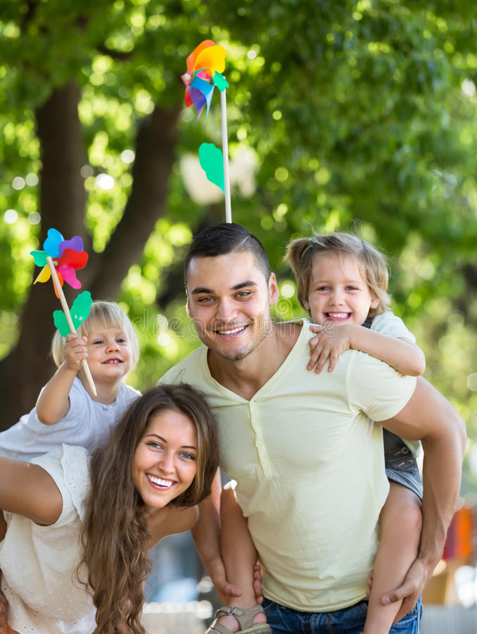 Family with toy windmills at park. Happy family holding kids with toy windmills at summer day stock image
