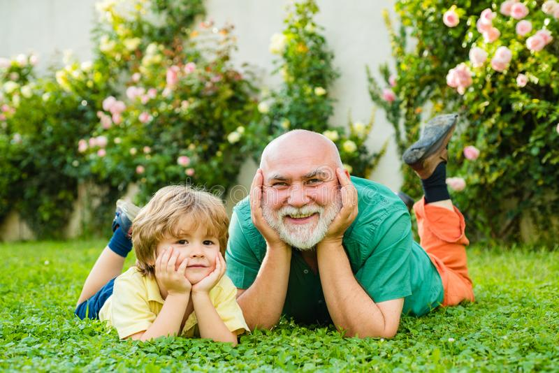 Family tradition. Concept of friendly family. Child with Grandfather dreams in summer in nature. Father son and royalty free stock image