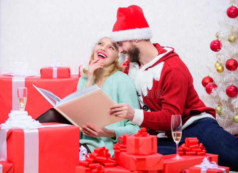 Family tradition. Couple in love enjoy christmas. Happy flashback. Family cuddle near christmas tree while looking. Family photo album. Remember bright moments royalty free stock photography