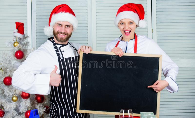 Family traditional menu for christmas dinner. Menu for our family. Man and woman chef santa hat near christmas tree hold royalty free stock photos