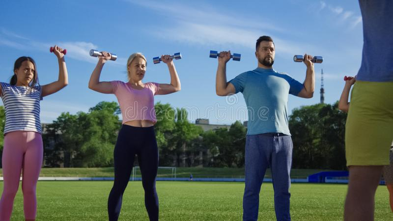 Family training with personal coach on field. Muscular tattooed personal trainer working out with adult couple and kids on green field in sunlight stock image