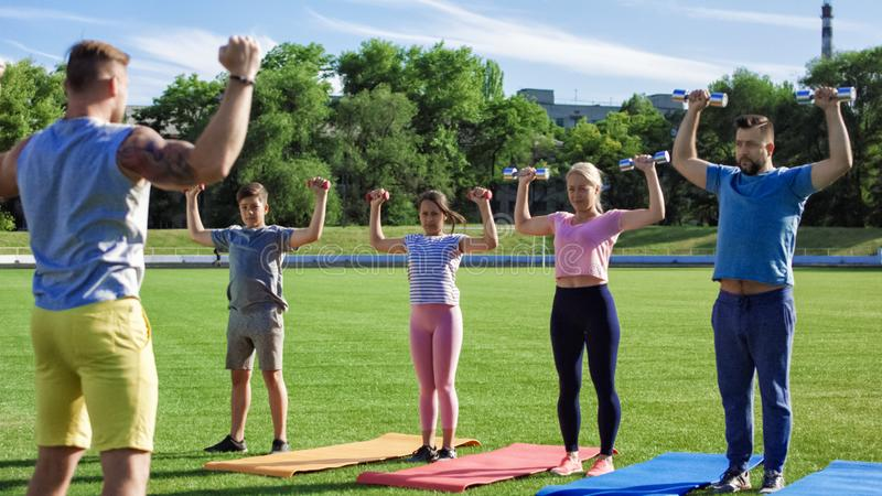 Family training with personal coach on field. Muscular tattooed personal trainer working out with adult couple and kids on green field in sunlight royalty free stock photography