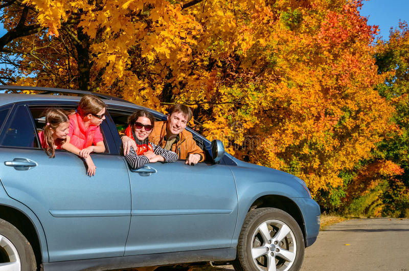 Family travel in car on autumn vacation, happy parents and kids have fun in trip. Insurance concept royalty free stock images