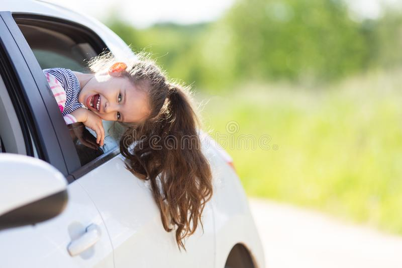 Family travel concept by car. Happy smiling child girl looking from the car window. Summer background. Soft focus.  stock photo