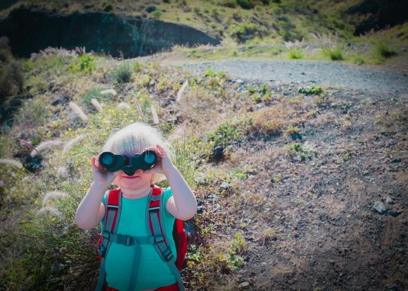 Family travel- little girl with binoculars exploring nature royalty free stock images