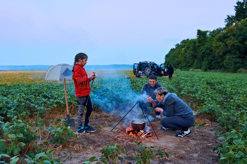Family traveling and camping, twilight, cooking on the fire. Beautiful nature - field, forest and moon royalty free stock image