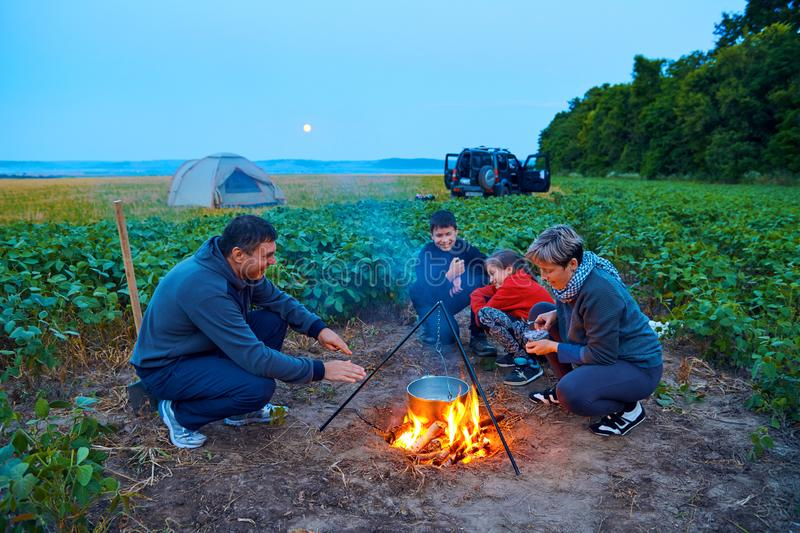 Family traveling and camping, twilight, cooking on the fire. Beautiful nature - field, forest and moon royalty free stock images