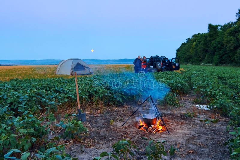 Family traveling and camping, twilight, cooking on the fire. Beautiful nature - field, forest and moon stock photo