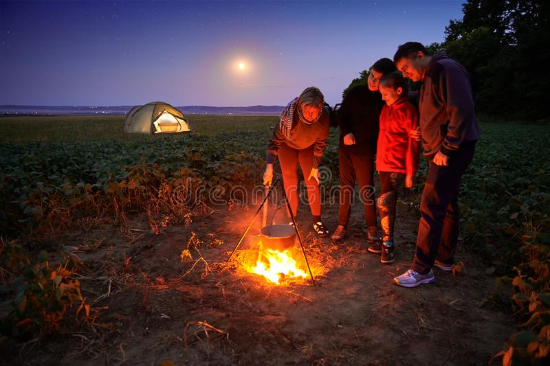 Family traveling and camping, twilight, cooking on the fire. Beautiful nature - field, forest, stars and moon royalty free stock images