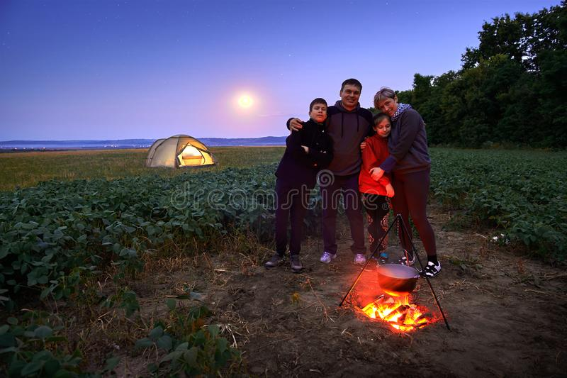 Family traveling and camping, twilight, cooking on the fire. Beautiful nature - field, forest, stars and moon stock photos