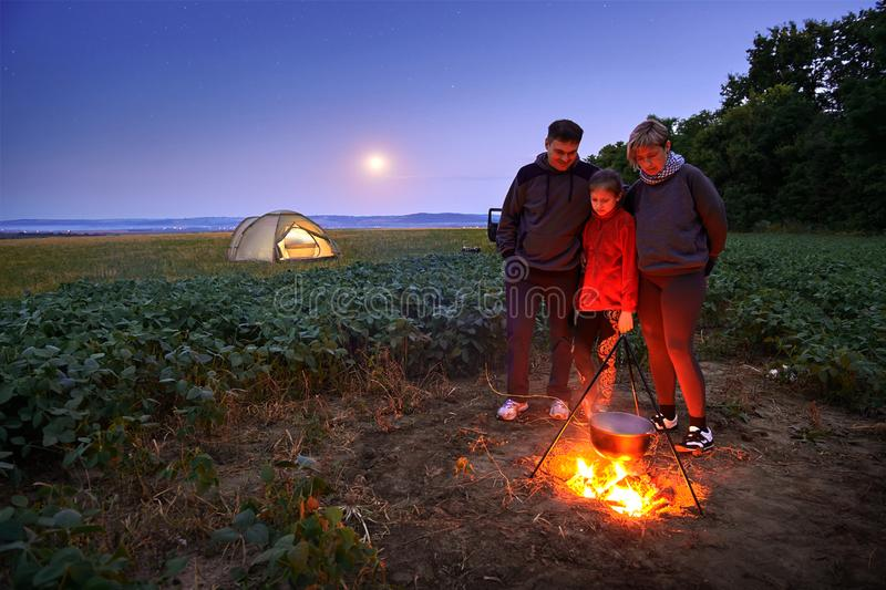 Family traveling and camping, twilight, cooking on the fire. Beautiful nature - field, forest, stars and moon royalty free stock photos