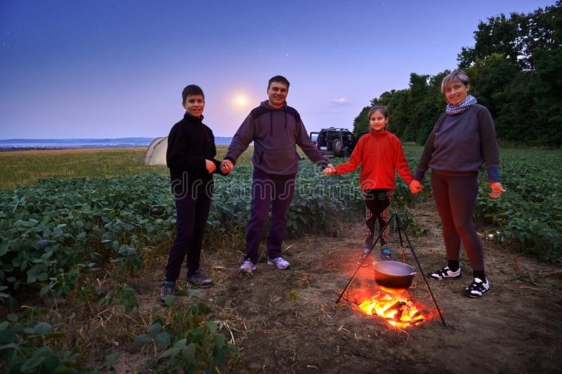 Family traveling and camping, twilight, cooking on the fire. Beautiful nature - field, forest, stars and moon stock image