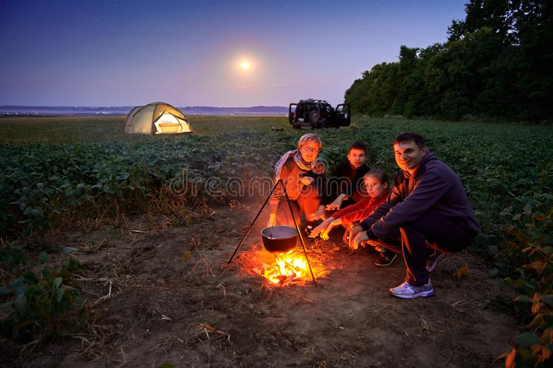 Family traveling and camping, twilight, cooking on the fire. Beautiful nature - field, forest, stars and moon stock images