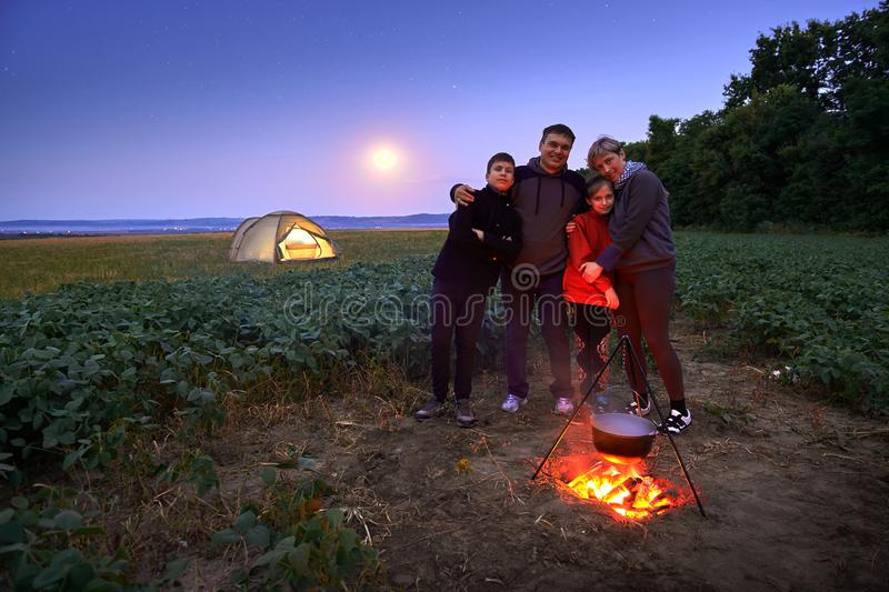 Family traveling and camping, twilight, cooking on the fire. Beautiful nature - field, forest, stars and moon stock photo