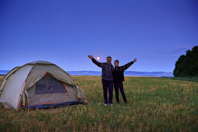 Family traveling and camping, twilight, posing near tent. Beautiful nature - field, forest, stars and moon. Father, son and girl royalty free stock photography