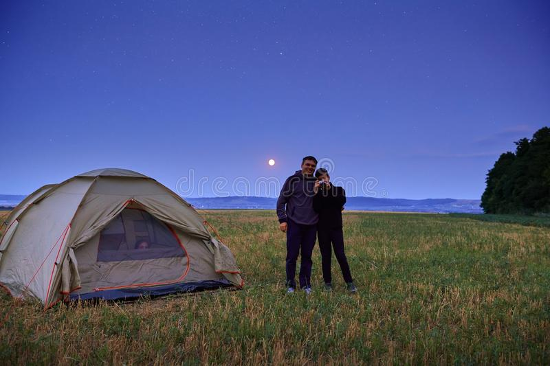 Family traveling and camping, twilight, posing near tent. Beautiful nature - field, forest, stars and moon. Father, son and girl stock image