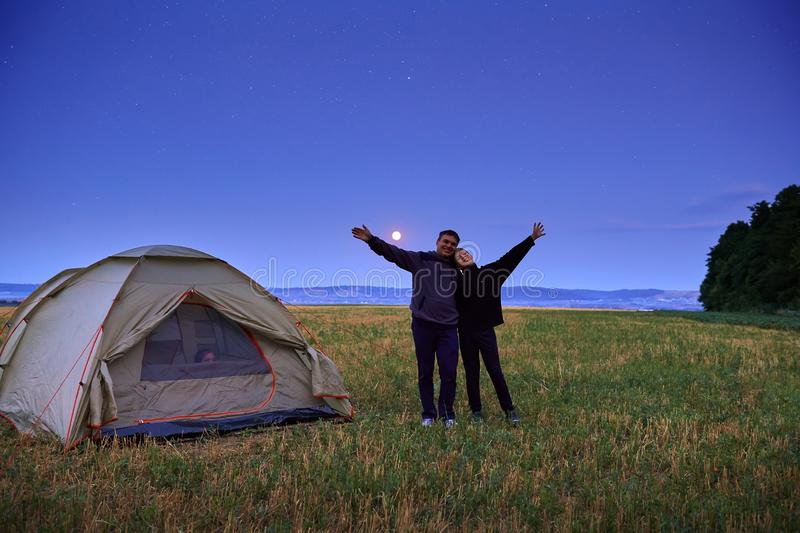 Family traveling and camping, twilight, posing near tent. Beautiful nature - field, forest, stars and moon. Father, son and girl stock photo