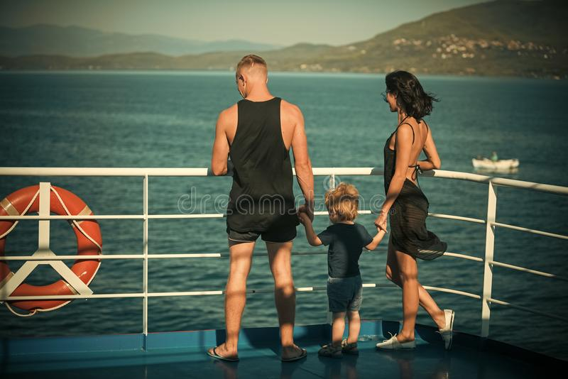 Family travelling on cruise ship on sunny day. Family with cute son on summer vacation. Father, mother and child stand stock image