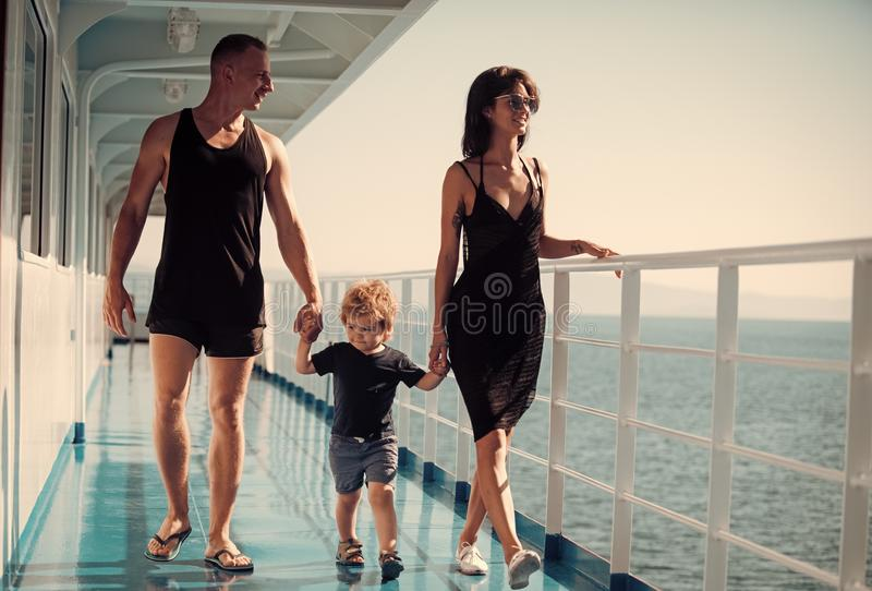 Family travelling on cruise ship on sunny day. Family with cute son on summer vacation. Family rest concept. Father. Mother and child walk on deck of cruise royalty free stock images