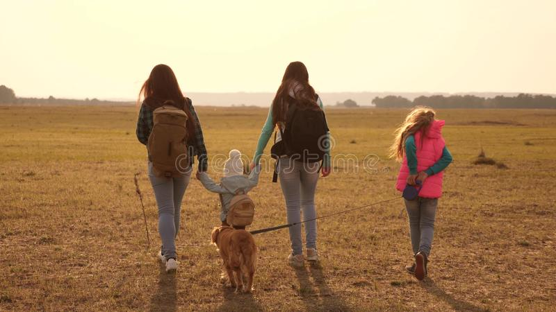 Family travels with the dog across the plains and mountains. mother, daughters and home pets tourists. teamwork of a stock photos