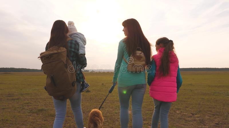 Family travels with the dog on the plain. teamwork of a close-knit family. mother, little child and daughters and pets. Family travels with the dog on plain stock photo