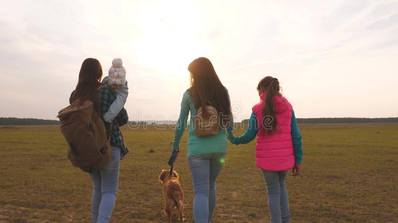 Family travels with the dog on the plain. teamwork of a close-knit family. mother, little child and daughters and pets. Family travels with the dog on plain stock photos