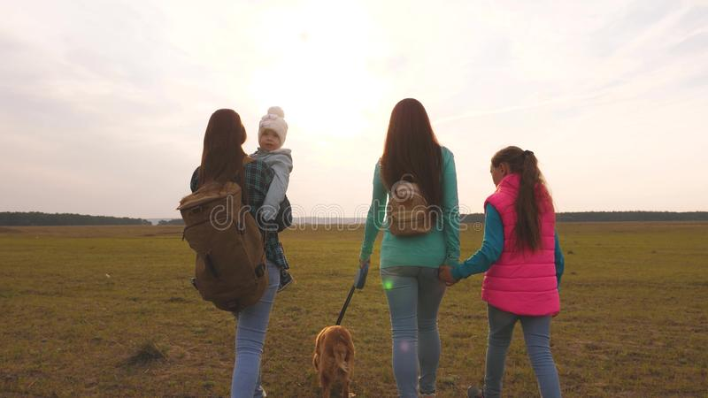 Family travels with the dog on the plain. teamwork of a close-knit family. mother, little child and daughters and pets. Family travels with the dog on plain stock image