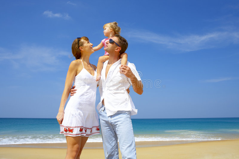 Family trip. Portrait of young family having fun on the beach royalty free stock images