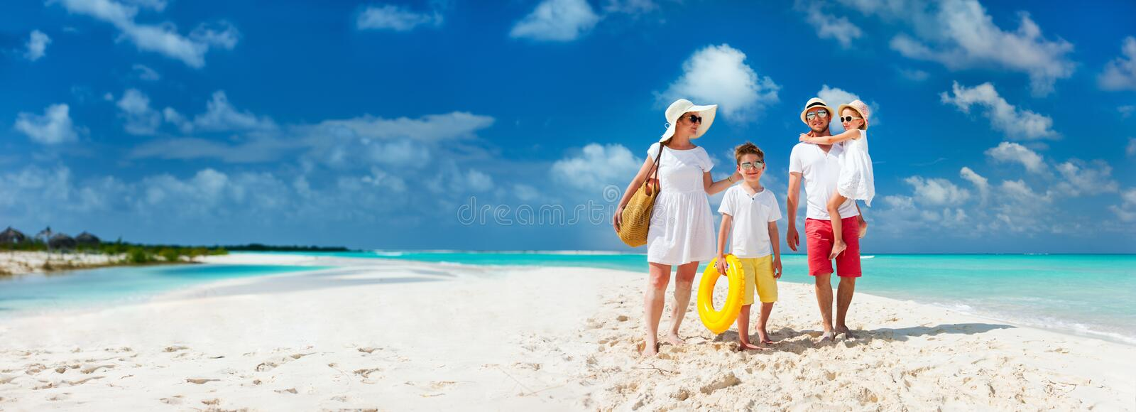 Family on a tropical beach vacation. Panorama of happy beautiful family with kids walking together on tropical beach during summer vacation