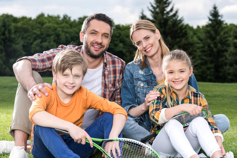 Family with two children holding badminton racquets and smiling at camera outdoors royalty free stock photo