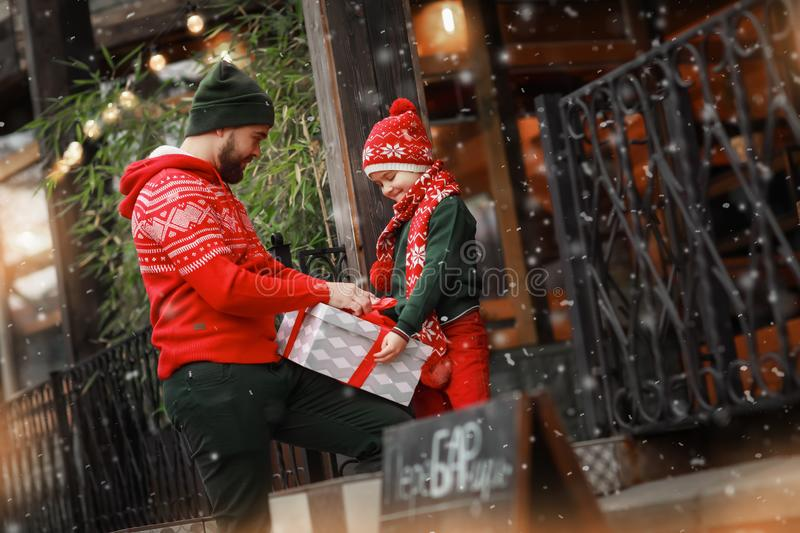 Family of two father and son are packing a gift box by tying it with a red ribbon. royalty free stock photos