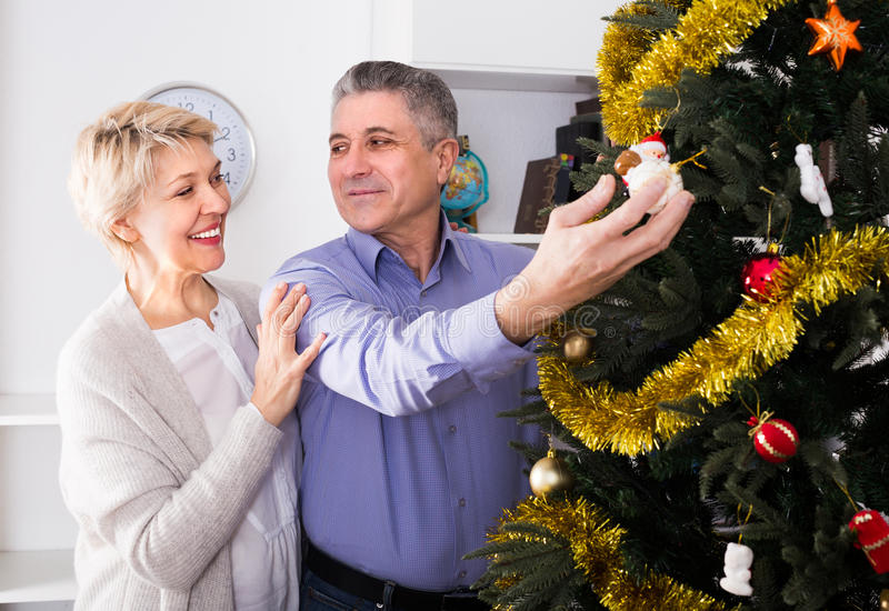 Family of two are hang up New Year`s toys on a fir-tree royalty free stock images