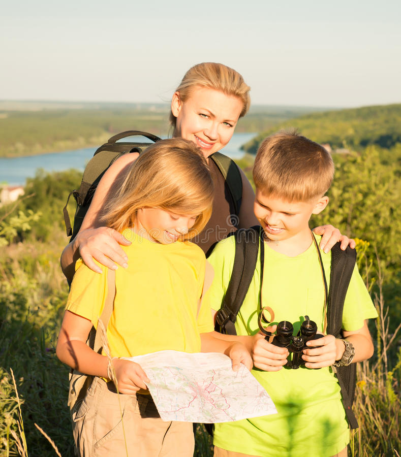 Family with two kids looking at map, family travel. Mother and c stock image