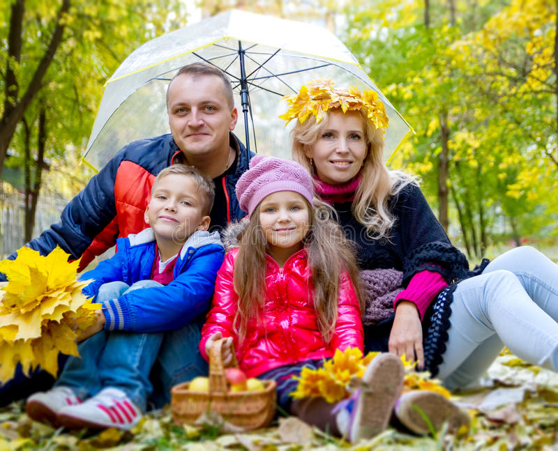 Family with two kids under umbrella and autumn leaves stock image