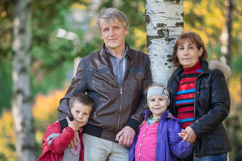 Family with two mature parents and son with daughter standing in park at autumn stock images