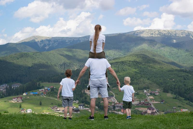 Family with two sons stands on a hill looking at the mountains. Summer day. Back view royalty free stock photos