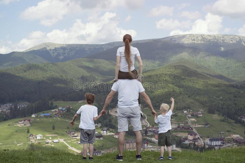 Family with two sons stands on a hill looking at the mountains. Summer day. Back view stock photo