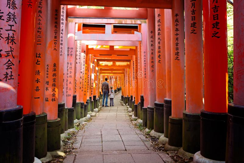 Fushimi inari in kyoto. Family of two standing and enjoying one of the famous sightseeing attractions in kyoto, japan - torii gates at fushimi inari stock images