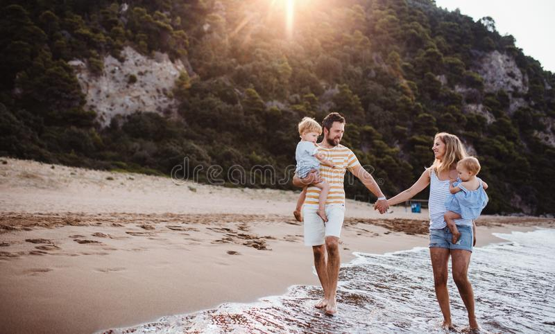 A family with two toddler children walking on beach on summer holiday at sunset. stock photo