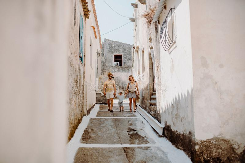 A family with two toddler children walking in town on summer holiday. A father and mother with son and daughter in baby carrier on a narrow street royalty free stock images