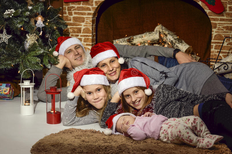 Family under the Christmas tree in the fireplace stock photos