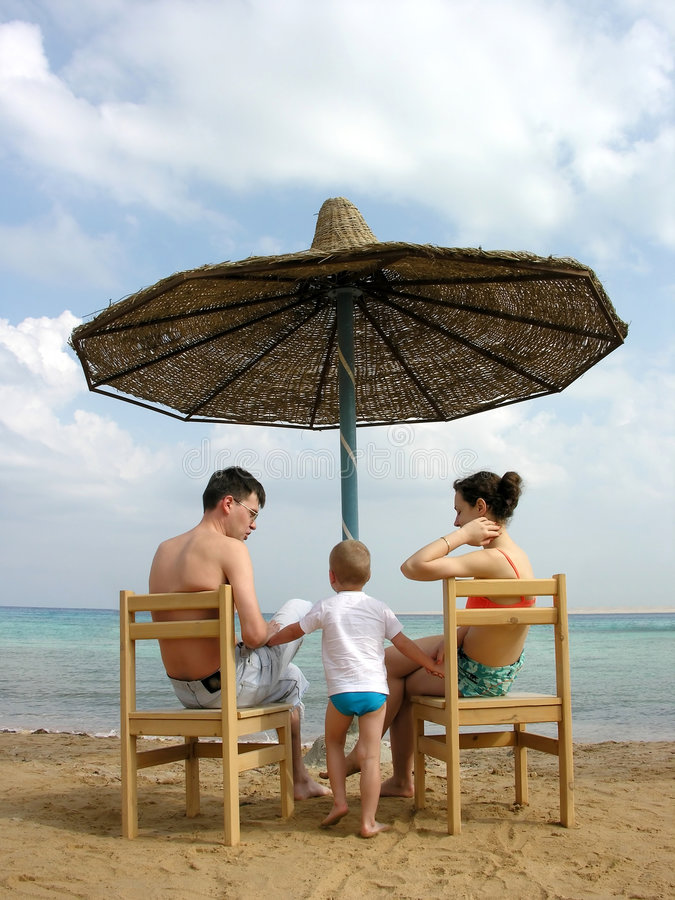 Free Family Under Umbrella On Beach Royalty Free Stock Images - 464769