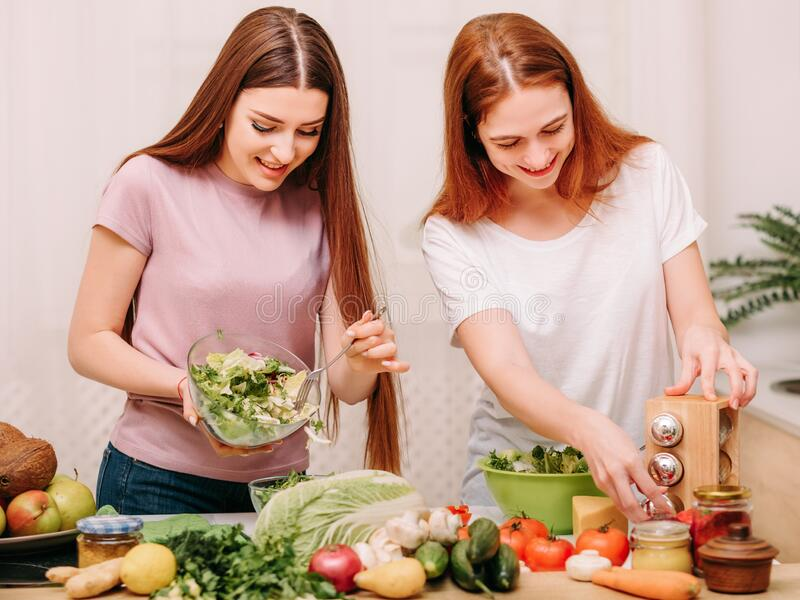 Family unity cooking leisure sisters salad kitchen. Family unity. Cooking leisure. Two sisters making salad with organic food ingredients in kitchen stock images